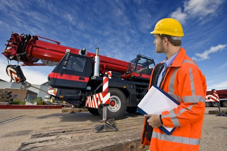 A maintenance engineer overlooking a huge mobile crane, the object of his inspection