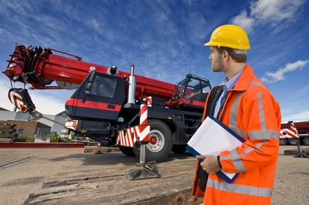Ein Wartungstechniker mit Blick auf eine große Mobilkran, das Objekt seiner Kontrolle