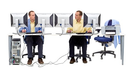 Two computer geeks working together behind a large desk, using several monitors Stock Photo - 4541476