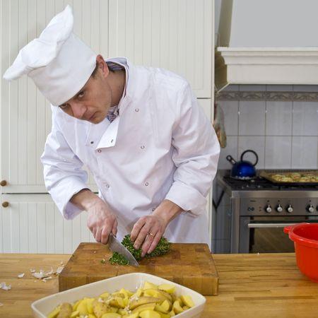 A chef preparing a potato oven dish, slicing thyme Фото со стока