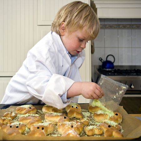 A small child decorating sweet bread with sprinklers