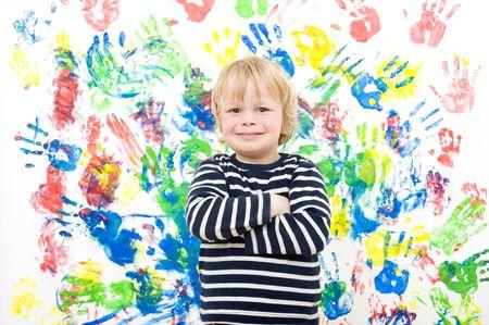 scoundrel: Un ragazzo in cerca orgogliosamente con le braccia incrociate, dopo aver completato la sua opera d'arte - pittura dito su un muro