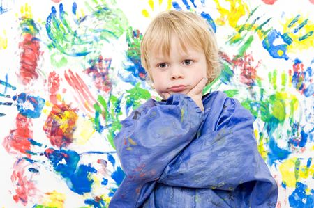 A young boy, looking snug and contented after making a colorful fingerpaint painting  photo