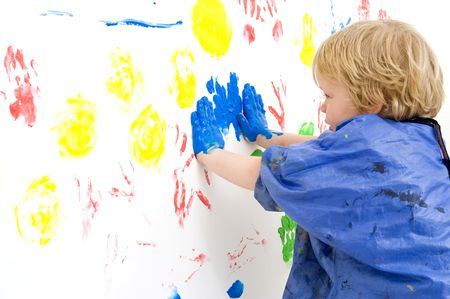 A young boy pressing his hands, covered with blue paint, against a wall, making prints with finger paint Stock Photo - 4678766