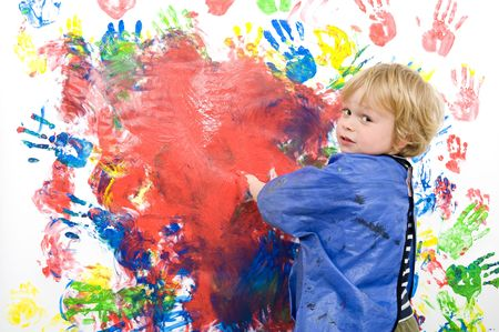 Young boy messing about with finger paint photo