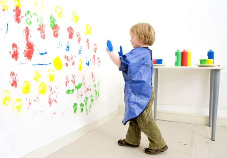 Painter boy approaching the wall hes finger painting on photo