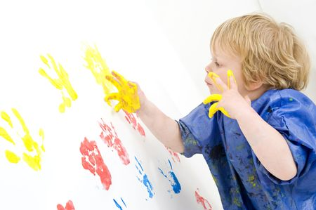 attentively: A young boy, attentively working on a finger painted painting on a wall