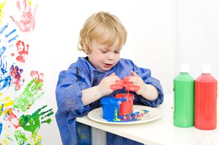 filthy: Boy with an apron playing with various colors finger paint