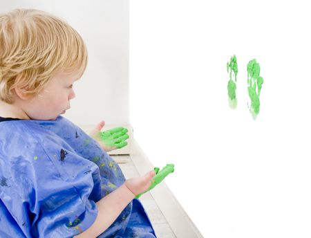 misbehaving: A young boy examining his mischief - the green hand prints he just made on a wall