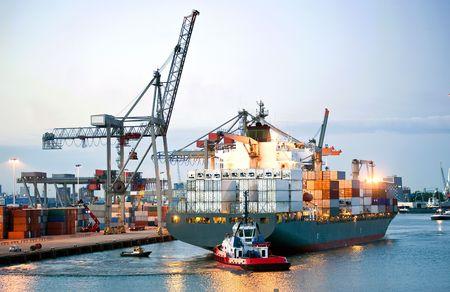 export and import: Ah enorme contenedor buque y maniobra hacia la costa por revertir los pilotos y remolcadores