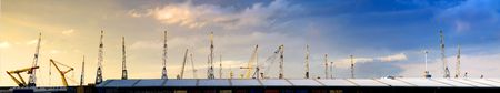erect: Panoramic image filled with a warehouse roof with cranes, sticking out like pins in a cushon with a natural gradient from yellow to blue in the sky due to the setting sun