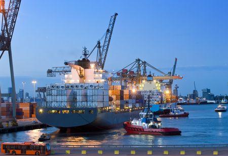containerschip: Verschillende sleepboten en ondersteunende vaartuigen, helpen een grote container schip Moor uit op de kade in de Rotterdamse haven. Een douane-voertuig en bemanning bus staan te escorte de bemanning door de douane en om de lading op de schemering