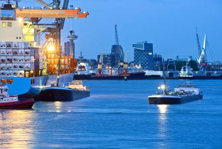 export and import: Enormes portacontenedores amarre frente, con varios arrastreros de suministro en torno a �l en un puerto comercial, con vistas a la ciudad de Rotterdam con el puente Erasmus, Euromast y varios altos edificios de oficinas