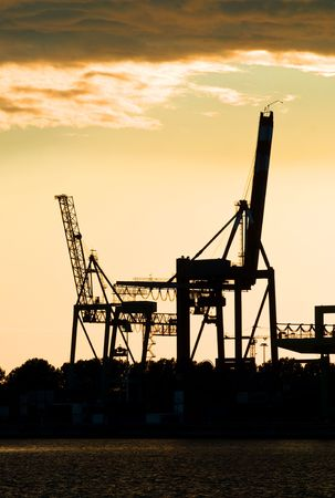 erect: Silhouettes of two motionless, erect, idle harbor cranes against the setting sun Stock Photo