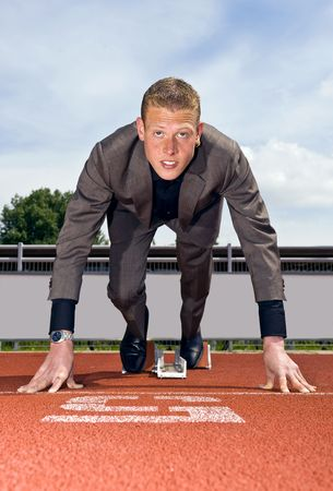 starting line: young businessman wearing a suit in the starting blocks to start building his career