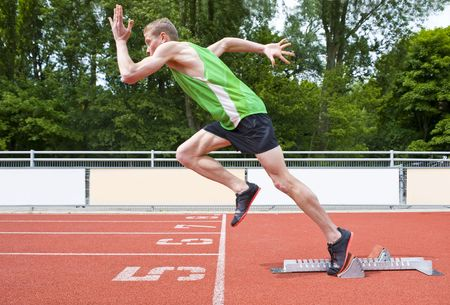 single track: Explosive start of an Athlete leaving the starting blocks on a sprint run