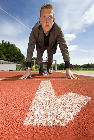 starting blocks: Being number one in business - businessman in the starting blocks on a running track in the first lane