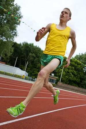 Running athlete on a middle distance race on an oval track in mid-air Stock Photo - 4983385
