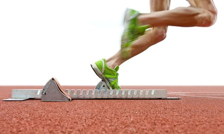 flexed: Action packed image of an athlete leaving the starting blocks for a sprint run on a track Stock Photo