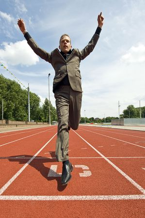 Metaphore for success in business - a business man crossing the finish line on an athletics track with his arms raised in victory