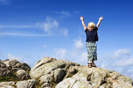 conquering: Young boy with his arms raised in victory on top of a rock, conceptual image for conquering challenges, pushing the boundaries, and continuous improvement