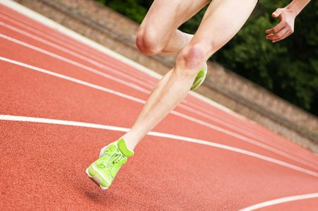 Legs and shoes of a long distance runner on an oval track photo