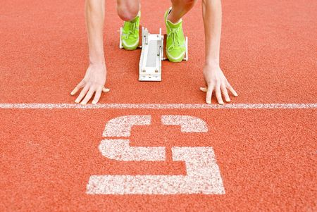 lean on hands: Athlete at the starting line in lane five, ready to go