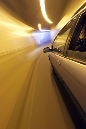 A car speeding, nearing the exit of a tunnel, seen from outside the vehicle photo