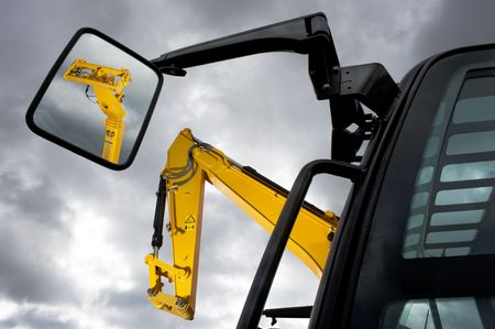 industry moody: Earth moving machines and forklift arms, one reflected in a side mirror, against a moody sky Stock Photo