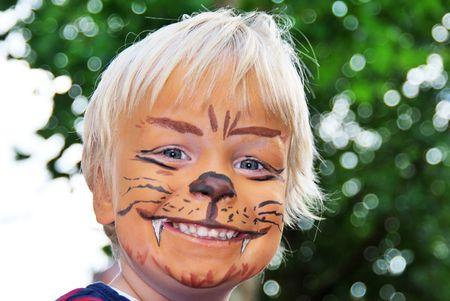 La cara sonriente de un ni�o pintado para parecerse a un le�n feroz Foto de archivo - 5486720
