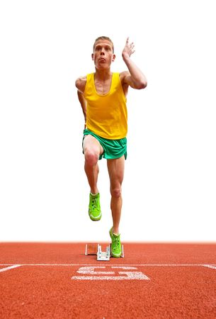 viewable: A young male runner is leaving the starting block in front of a white background. He is looking up and away from the camera and is viewable full length. Vertically framed shot.