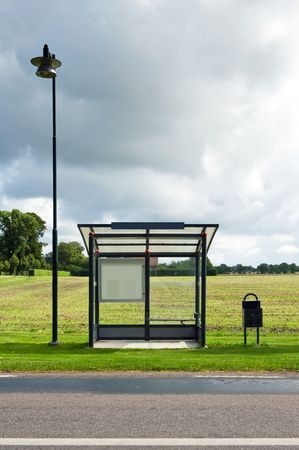viewable: A bus stop is depicted standing in front of a field. Dark clouds indicate a storm is coming. There is no one viewable in the image. Vertically framed shot.