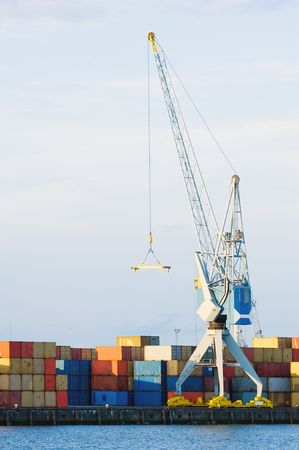 viewable: A large cargo crane stands at port in front of stacks of containers. There is no one viewable in the image. Vertically framed shot.