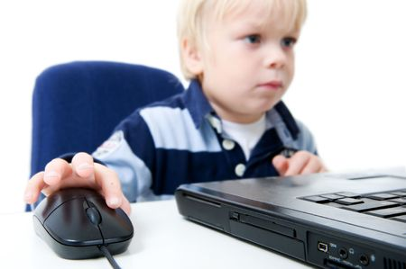 viewable: A young boy sits using a laptop computer. He is viewable from the chest up, looking away from the camera, and the focus is on the laptop and mouse. Horizontally framed shot, focus on hand and computer mouse