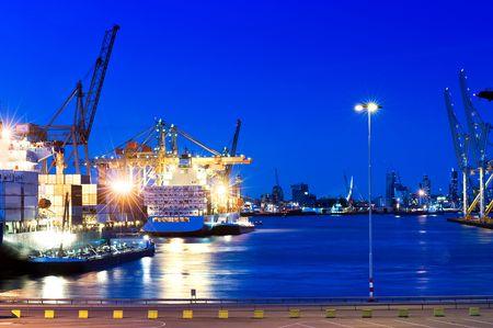 Afbeelding van een haven stad met intensieve blauwe verzadigde kleuren. Boten op het water, en de stad van Rotterdam is zichtbaar in de achtergrond. Geen mensen. Horizont aal geframede doodgeschoten.