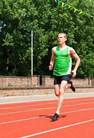 A young male athlete runs on a track. He is viewed full length, and he is looking away from the camera. Vertically framed shot. photo