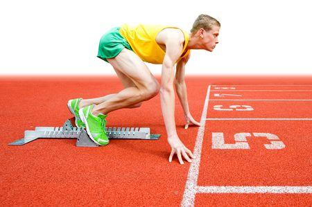 A young male runner crouches in the 'start' position. His is viewed full length and in profile. Horizontally framed shot. photo