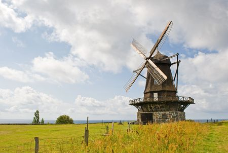 viewable: An old windmill is shown in a rural area. There are no people viewable. Horizontally framed shot. Stock Photo