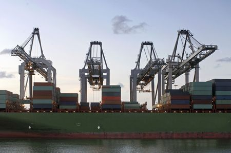 simultaneously: Four huge cranes simultaneously unloading a container ship at dusk Stock Photo