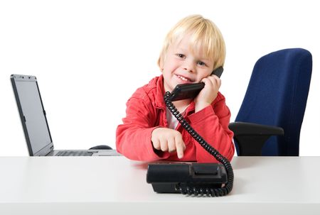 sparce: Young blond boy wearing a red sweater dialling on a phone in a sparce office