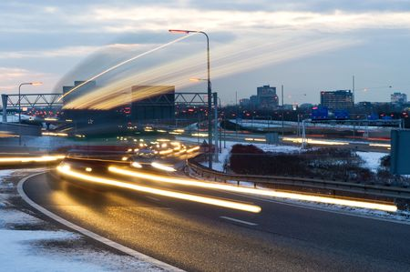 Cars passing by on a motorway junction on a winter evening photo