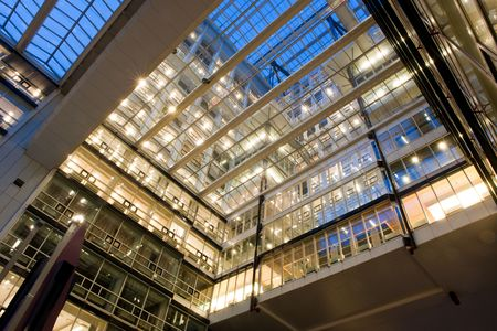Modern offices at dusk, with various floors, clean, straight lines and a glass roof, looking up to the sky Stock Photo