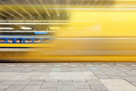 Train departing from a platform, leaving a blur and a glimpse on a waiting train on another platform  photo