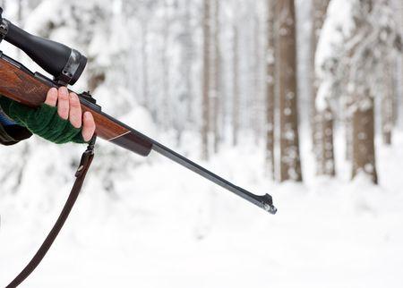 Main d'un chasseur, tenant un fusil dans une forêt d'hiver