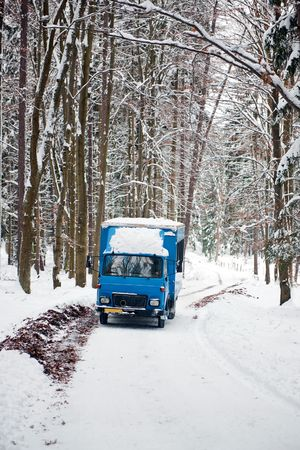 An old soviet truck driving on a snowy road through a forest in the Czech republic photo