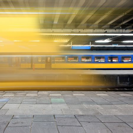 Train arriving at a platform, leaving a blur and a glimpse on a waiting train on another platform  photo
