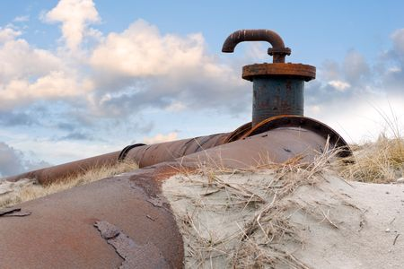 flanges: An old, obsolete pipeline with a faucet and flanges, surrounded by the drift-sand and marram grass of the dunes against a radiant cloudscape. Stock Photo