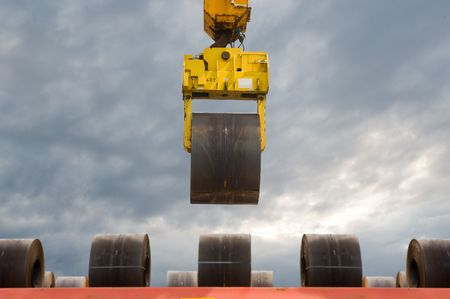 designated: An overhead crane carrying a steel coil to a designated place in an automated outdoor storage facility.