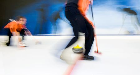 curling: Two players of a curling team  delivering a stone, brushing to adjust the precision and the curvature of the stone