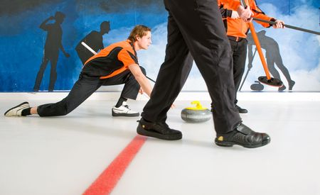 curling: Curler, gliding on the ice, delivering a stone, with two sweepers, to act on the Skips request Stock Photo